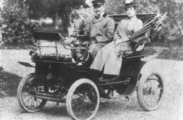 Man and woman sit in old convertible car from the early 1900's